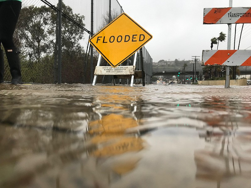 Traffic signs are shown on flooded roads in Mission Valley during a winter st...