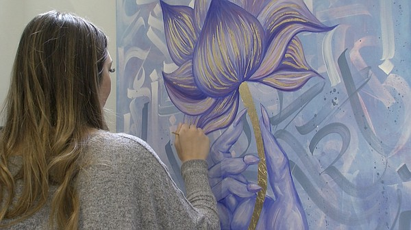 Artist Kaitlyn Alfaro works on one of her paintings at Th...