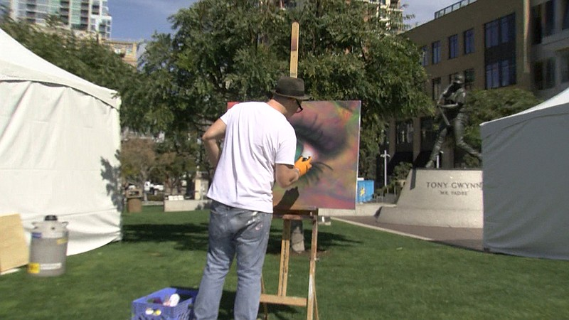 An artist works on a graffiti painting at the San Diego Festival of Science A...