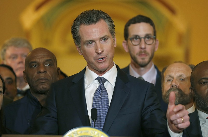 Flanked by lawmakers, Gov. Gavin Newsom discusses his decision to place a mor...