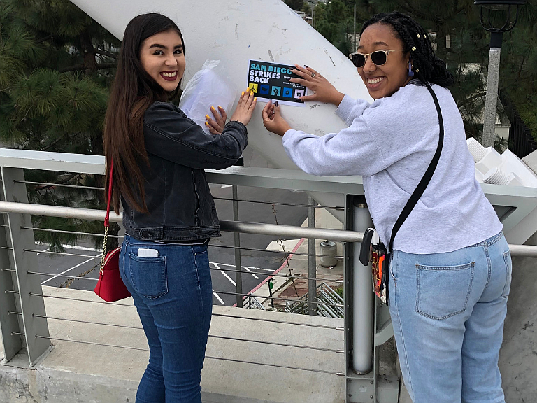 Kate Anchondo (left) and Rachal Hamilton (right) posting flyers about a Youth...
