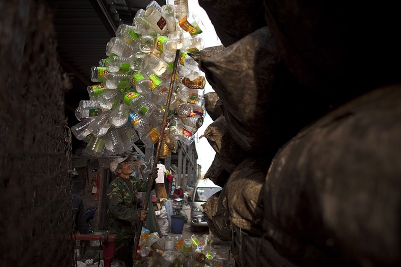 A worker loads used plastic bottles on a truck at a recycling center in Beiji...