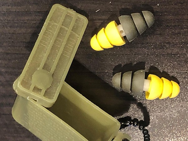 Dual-ended Combat Arms earplugs are displayed on a table ...
