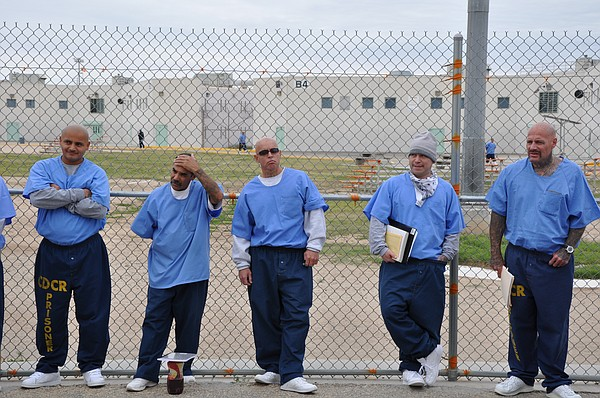 Inmates wait to enter a classroom at Centinela State Pris...