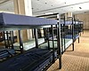 Bunk beds line a communal sleep area at a new, ...