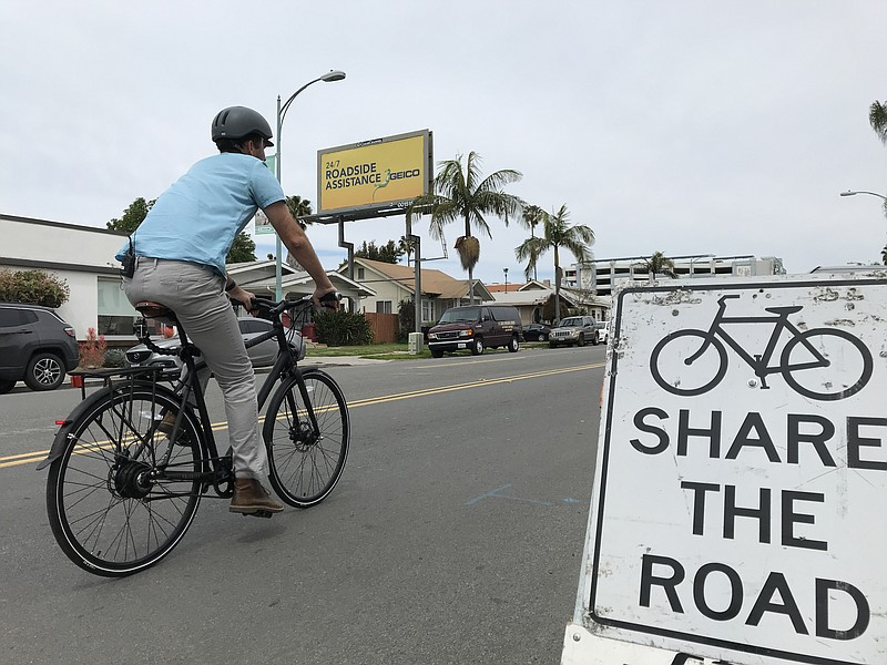 Matt Stucky rides his bike up 30th Street in North Park past a sign that read...