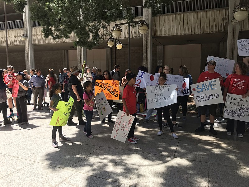 San Diego residents hold signs at a demonstration in support of saving Skatew...