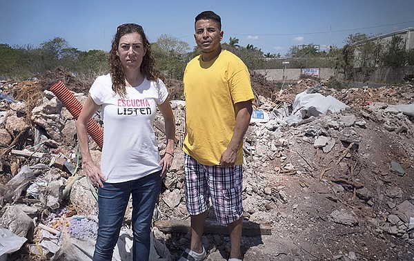 Elizabeth and Marcos standing amidst the rubble in the Yu...