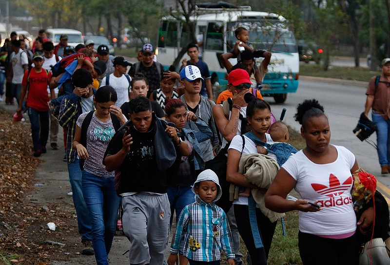Migrants walk along a highway as a new caravan of several hundred people sets...