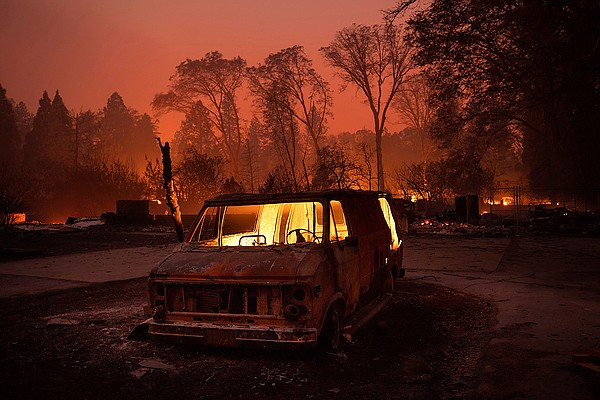 Flames burn inside a van as the Camp Fire tears through P...