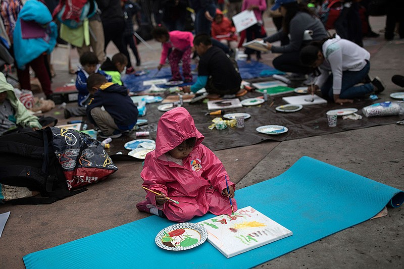 A Guatemalan child paints at the El Chaparral U.S.-Mexico border crossing, in...