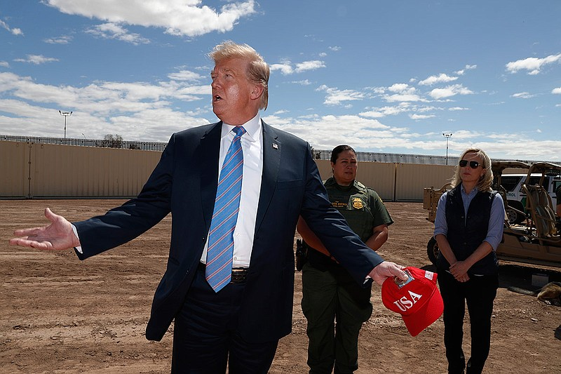 President Donald Trump visits a new section of the border wall with Mexico in...