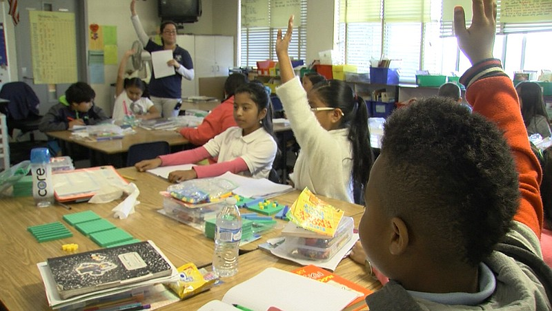 Donnell Branch, right, raises his hand in his Perkins Elementary Schoool four...