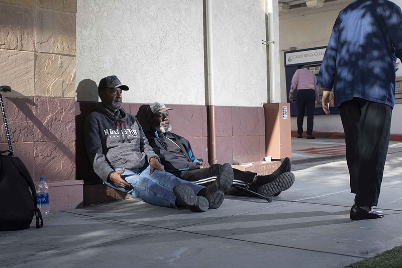 Carl Russell sits next to his homeless friend, Oscar Walker, in downtown San ...