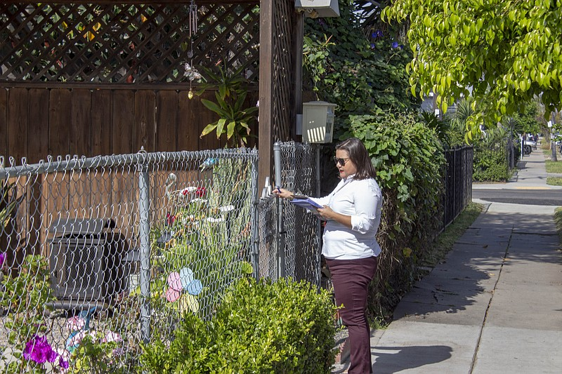 City Councilwoman Vivian Moreno opens a gate while canvassing in the Stockton...