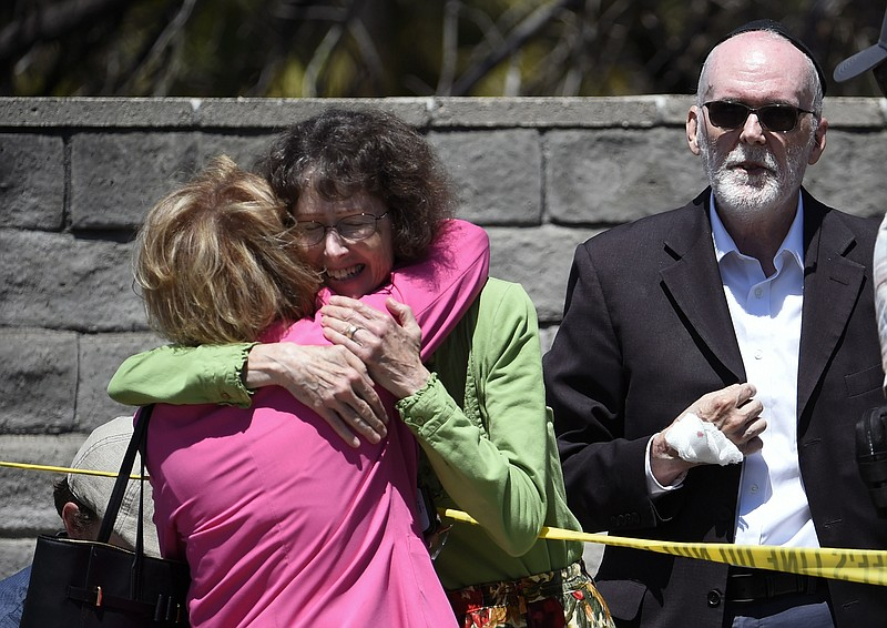 Synagogue members hug as a man with a hand injury looks on outside of the Cha...