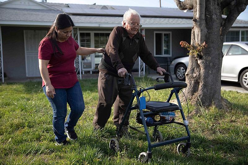 Cristina Hernandez walks with her dad Francisco Rios, 91, across the lawn at ...