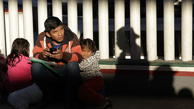 A migrant and his children wait to hear if their number is called to apply fo...