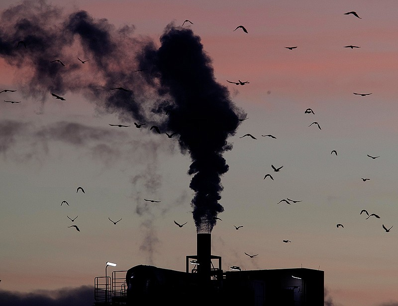 In this Dec. 4, 2018, file photo, birds fly past a smoking chimney in Ludwigs...