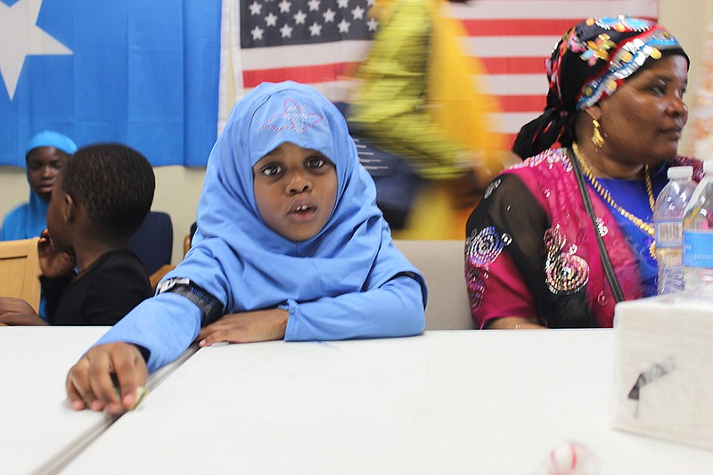 A young Muslim girl learns about the tradition of Eid al-Fitr at the Somali B...