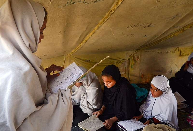 Afghan students attend an under tent class in Jalalabad, capital of Nangarhar...