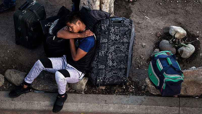 An asylum seeker rests outside El Chaparral port of entry while he waits for ...
