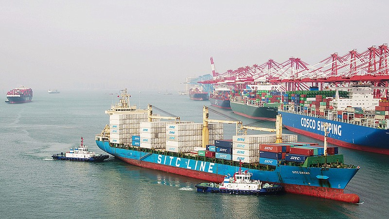 A cargo ship prepares to berth at a port in Qingdao in China's eastern Shando...