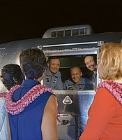 The Apollo 11 crewmen, still under a 21-day quarantine, are greeted by their wives. Looking through the window of a Mobile Quarantine Facility are (left to right) astronauts Neil A. Armstrong, Edwin E. Aldrin, Jr., and Michael Collins. The wives are (left to right) Mrs. Pat Collins, Mrs. Jan Armstrong, and Mrs. Joan Aldrin. July 27, 1969.
