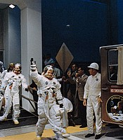 The crewmen of the Apollo 11 lunar landing mission leave the Kennedy Space Center's Manned Spacecraft Operations Building during the prelaunch countdown. Astronauts Neil A. Armstrong, Commander; Michael Collins, Command Module Pilot; and Edwin E. Aldrin Jr., Lunar Module Pilot, ride the special transport van over to Launch Complex 39A where their spacecraft awaited them. July 16, 1969.