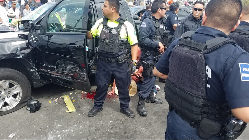 Mexican law-enforcement officials and first-responders at the aftermath of an...