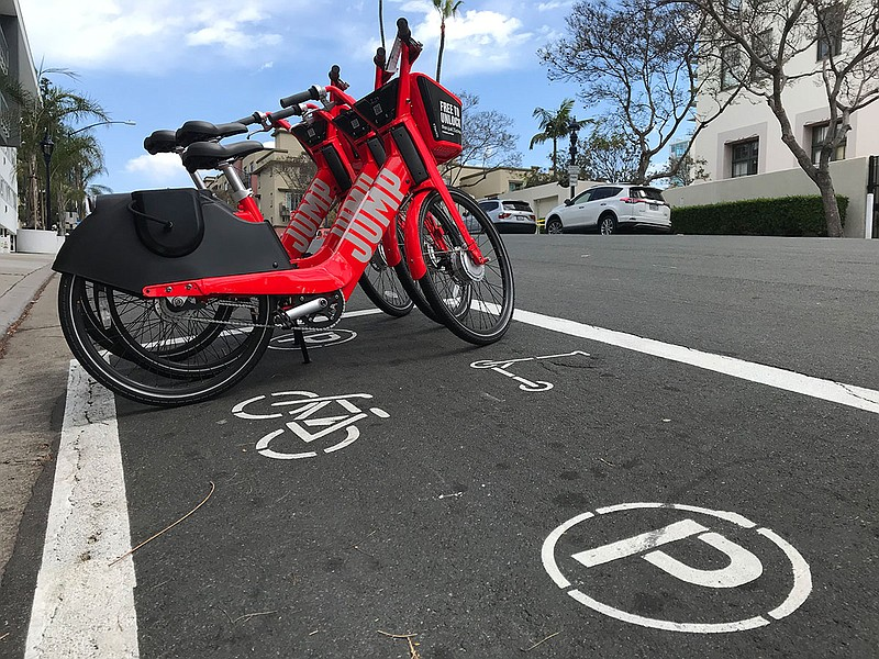 Electric bikes are seen parked in a newly painted dockless bike and scooter p...