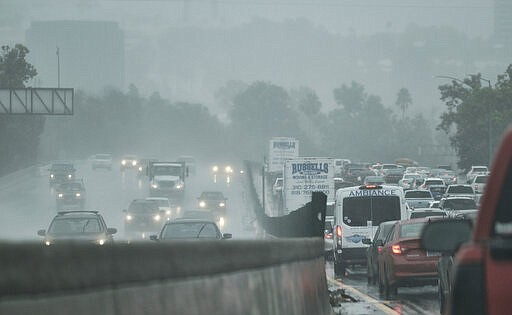 Drivers make their way in the pouring rain along the Hollywood Freeway in Los...