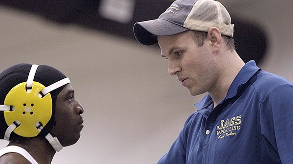 Jamario Rowe (left) gets advice from Coach Scribner durin...