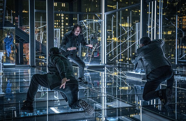 John Wick (Keanu Reeves) faces off against the students (...