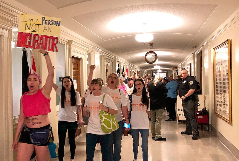 Protesters march through the halls of the Missouri Capitol outside the House ...