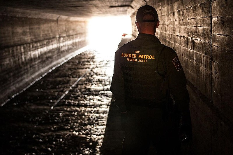 A Border Patrol agent inspecting a water drainage tunnel that spans from Noga...