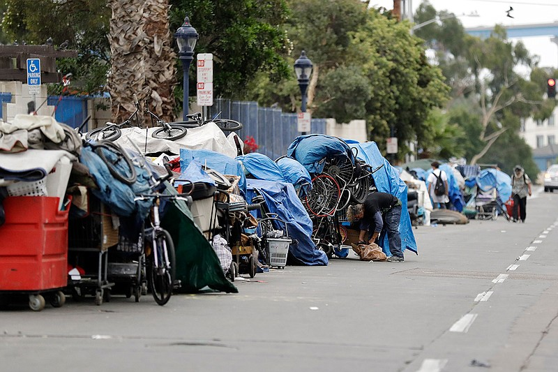 Homeless people stand among their items along 17th Street in San Diego, Sept....