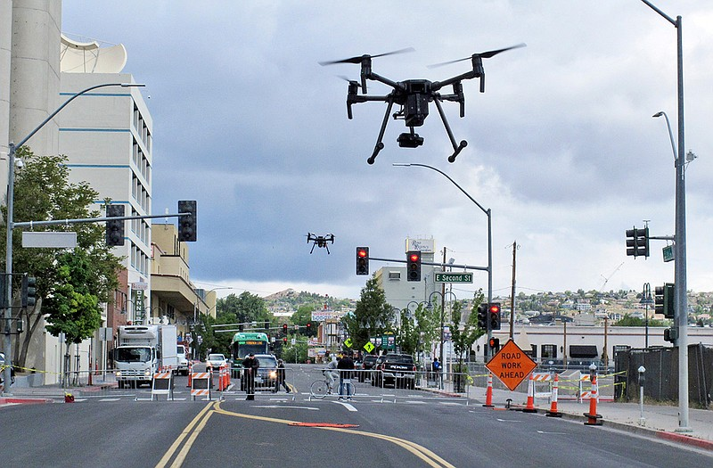 In this May 21, 2019 photo, two drones fly above Lake Street in downtown Reno...