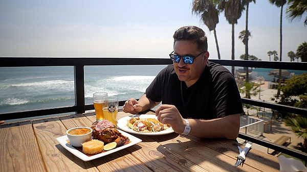 Host Jorge Meraz tastes beer and the food at Sin Frontera...