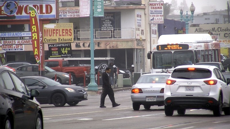 A pedestrian surrounded by cars crosses El Cajon Boulevard in City Heights, J...