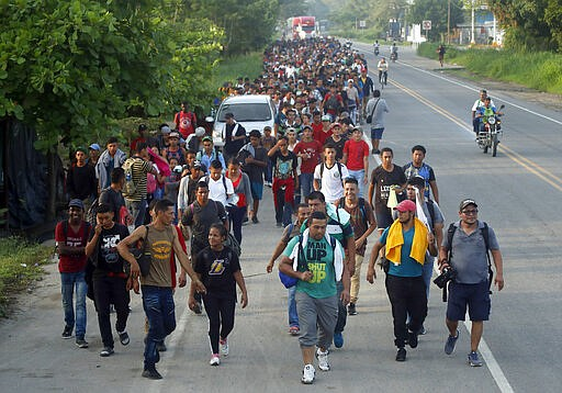 Hundreds of Central American migrants walk on the highway, after crossing the...