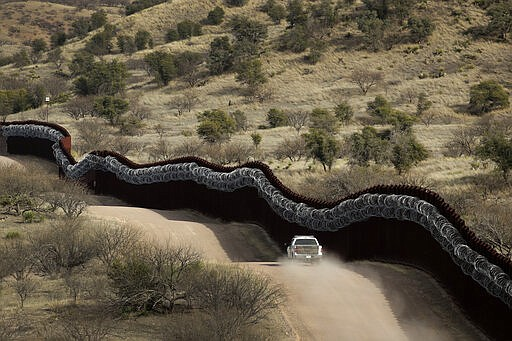 A Customs and Border Control agent patrolling on the US side of a razor-wire-...