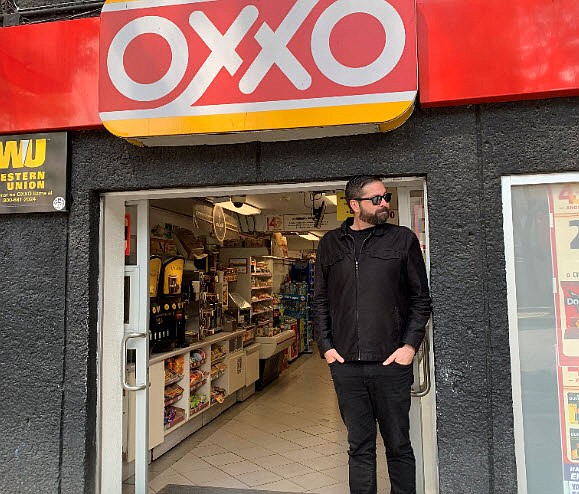 Photographer John Brady stands in front of an Oxxo convenience store in Tijua...