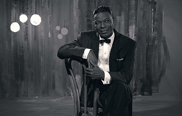 Black and white photo of Nat King Cole sitting on a cockt...