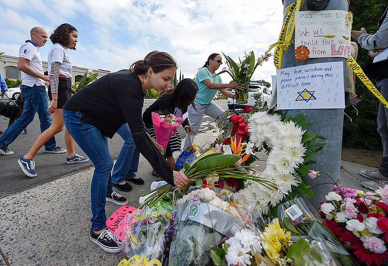 A group of Poway residents bring flowers and cards to a memorial outside of t...