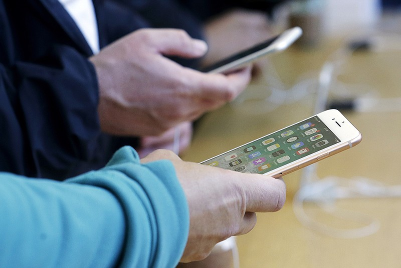In this Sept. 22, 2017, file photo, customers look at iPhones at an Apple Sto...