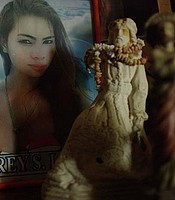 A photograph of Jennifer Laude in a picture frame sits on a table next to statues.