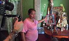 """Julita """"Nanay"""" Laude is filmed while holding a ..."""