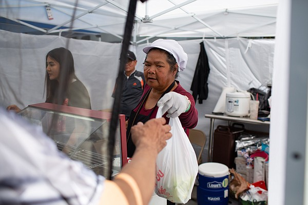 Customers buy Thai food from a stall at the East Hollywoo...