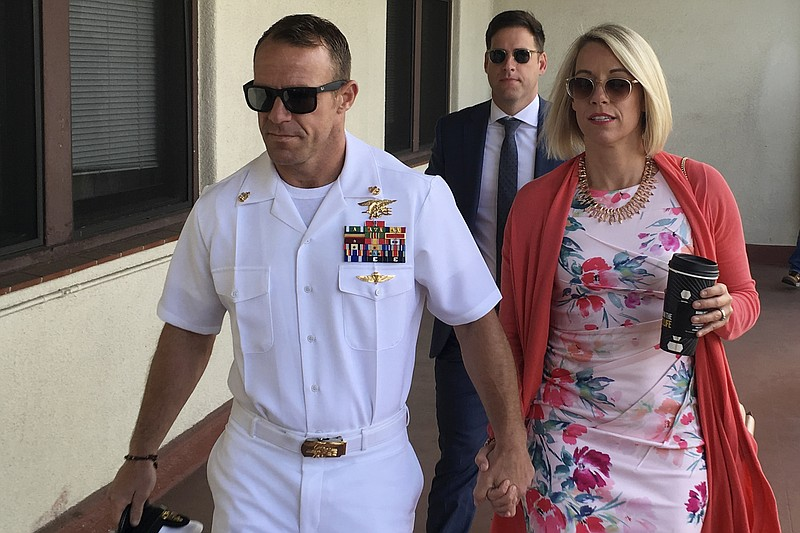 Navy Special Operations Chief Edward Gallagher, left, walks with his wife, An...